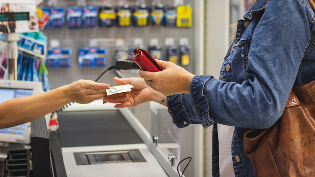 Woman holding a wallet and paying in a cash at shop. Check out in supermarket store.