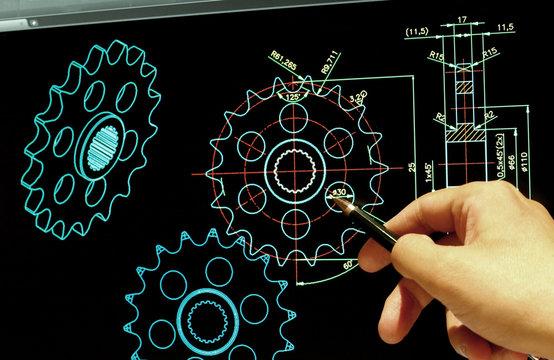 engineer working on computer at mechanical gear design cad blueprints