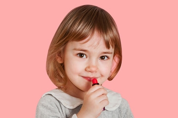 Portrait of smiling little baby girl paints lips with lipstick isolated on a pink background.