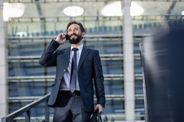 Low angle of a cheerful businessman talking on phone