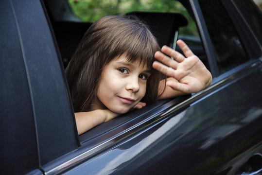little girl waving through the car window, goodbye concept