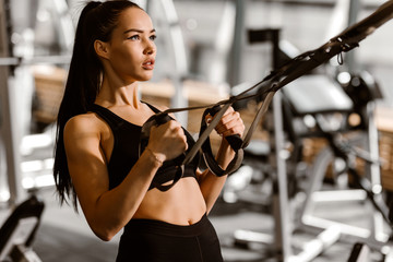 Athletic dark-haired  girl dressed in black sports top and shorts is working out on the fitness-station in the gym