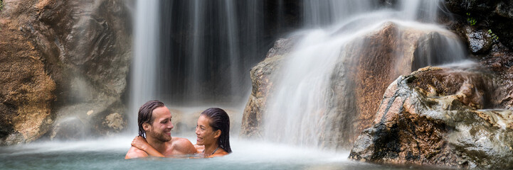Wall Mural - Vacation couple relaxing in waterfall banner. Romantic destination travel holidays people happy together swimming under natural water falls.