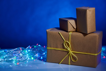 few simple craft Christmas boxes with lights on blue background