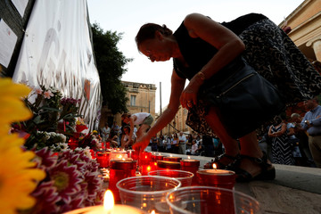 People lay flowers and candles at a makeshift memorial to assassinated anti-corruption journalist Daphne Caruana Galizia during a vigil to mark eleven months since her murder in a car bomb, in Valletta