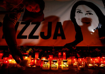 A woman places a candle at a makeshift memorial to assassinated anti-corruption journalist Daphne Caruana Galizia during a vigil to mark eleven months since her murder in a car bomb, in Valletta