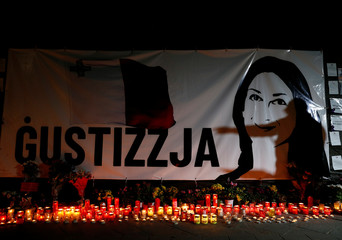 """Activist and blogger Manuel Delia addresses people at a vigil to mark eleven months since the assassination of anti-corruption journalist Daphne Caruana Galizia in a car bomb, in front of a banner reading """"Justice"""" at a makeshift memorial in Valletta"""