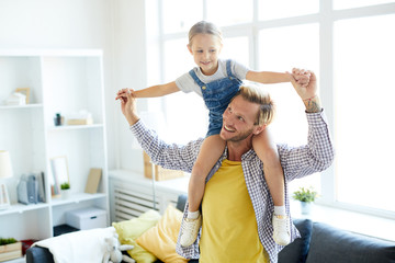 Happy dad holding his little daughter by hands while keeping her on his shoulders during play