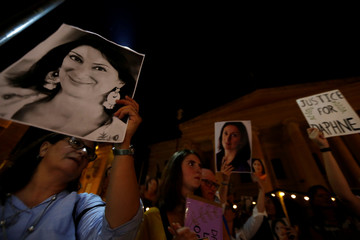 Family members of assassinated anti-corruption journalist Daphne Caruana Galizia hold photos of her during a vigil to mark eleven months since her murder in a car bomb, in Valletta