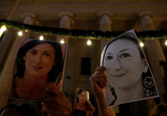 People hold photos of assassinated anti-corruption journalist Daphne Caruana Galizia during a vigil to mark eleven months since her murder in a car bomb, outside the Courts of Justice in Valletta