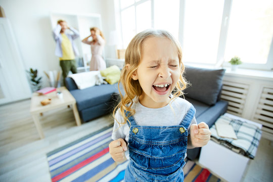 Youthful daughter crying and screaming loudly while being naughty with her shocked parents on background