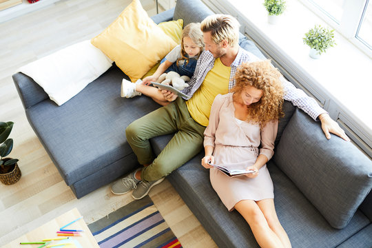 Overview of relaxed family of three sitting on sofa, reading and watching online movie on weekend