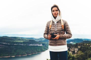 photographer tourist traveler standing on top mountain holding in hands digital photo camera, hiker taking click photography, girl enjoy nature panoramic landscape in trip, relax holiday hobby concept