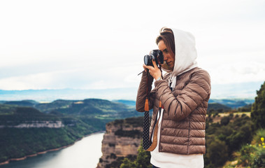 photographer traveler on green top on mountain, tourist looking holding in hands digital photo camera, hiker taking click photography, girl enjoy nature landscape in trip, relax holiday hobby concept