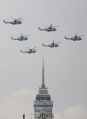A formation of military helicopters fly over Zocalo Square during a military parade to celebrate Independence Day in Mexico City