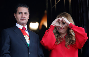 Mexico's President Enrique Pena Nieto looks on as first lady Angelica Rivera makes a hand heart gesture during a military parade to celebrate Independence Day in Mexico City