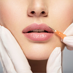 young woman gets botox injection in her lips