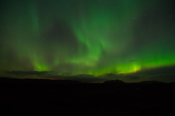 northern lights above reykjavik, iceland. polar lights or northern wand in reykjavik, iceland. beautiful green illumination in sky of northern light in iceland. tourism and travel. pure beauty.