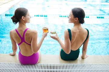Two wet females with cocktails toasting for their summer vacation while sitting by swimming-pool