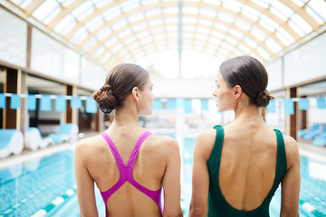 Wet backs of two young fit females in swimwear standing in front of swimming-pool in spa center