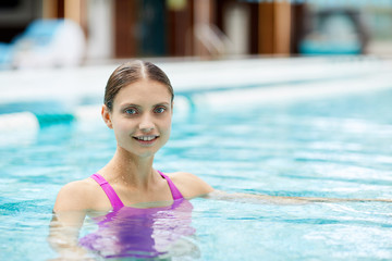 Young blonde woman looking at you while enjoying spa swimming at summer resort