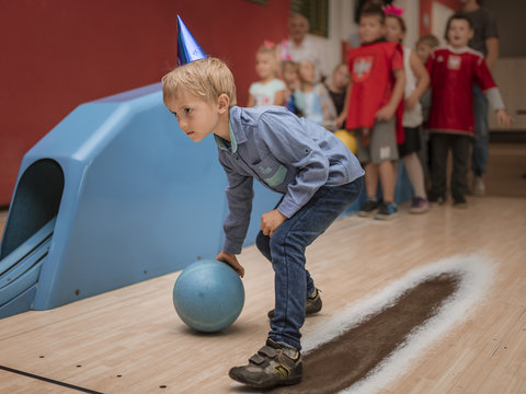 Six years old boy playing bowling during birthday party.
