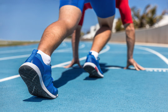 Sprinter waiting for start of race on running tracks at outdoor stadium. Sport and fitness runner man athlete on blue run track with running shoes.