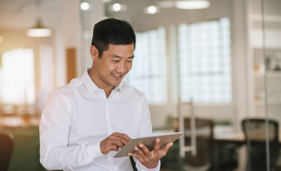 Smiling Asian businessman working with a tablet at work