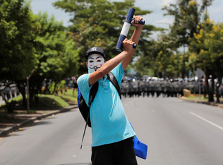 A masked anti-government protester holds a homemade mortar in front of a line of riot police during a protest against Nicaraguan President Daniel Ortega's government in Managua
