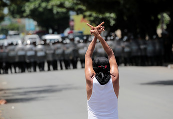 A masked anti-government protester gestures in front of a line of riot police during a protest against Nicaraguan President Daniel Ortega's government in Managua