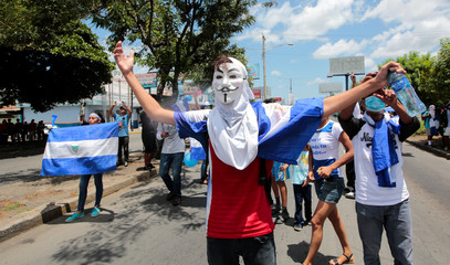 A masked anti-government protester shouts slogans to riot police during a protest against Nicaraguan President Daniel Ortega's government in Managua