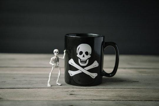 Small Skeleton Posed Beside a Halloween Mug