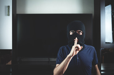 Thief with black balaclava making silence gesture.