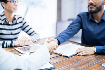 Close-up of two businessmen sitting at table and shaking hands during a meeting at office