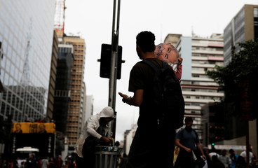 Daughter of a PT supporter plays with a mask depicting Brazil's former President Lula da Silva during presidential candidate Haddad's campaign rally in Sao Paulo