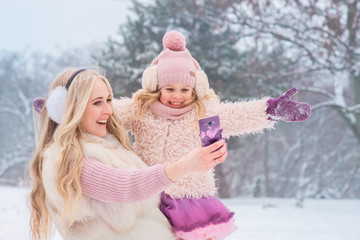 mom blonde and little daughter dressed in pink clothes have fun and do selfie on a mobile phone