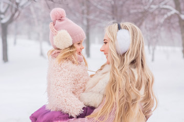 mother with long blond curls hugs her beautiful little daughter in a pink hat with a bubo