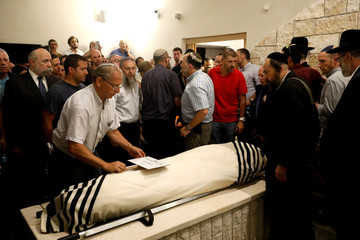 Relatives and friends mourn during the funeral of Ari Fuld at a cemetery in Kfar Etzion