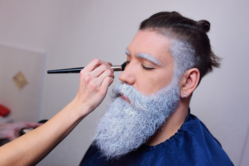make-up artist does makeup to a man with a white or gray beard.