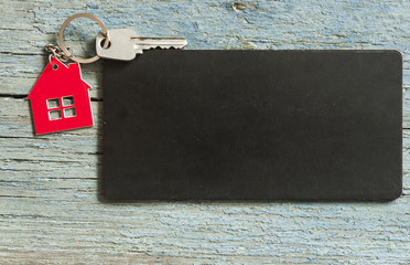 blank blackboard and symbol of the house with silver key on vintage wooden background