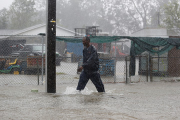 A man walks down a flooded street in downtown during Tropical Storm Florence in Dillon