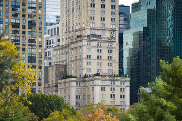 Close-up view of some skyscrapers in Manhattan and some coloured trees in the foreground. New York, USA.