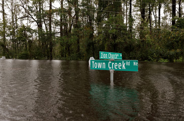 Street signs are mostly submerged by rising flood waters in the aftermath of Hurricane Florence in Leland, North Carolina