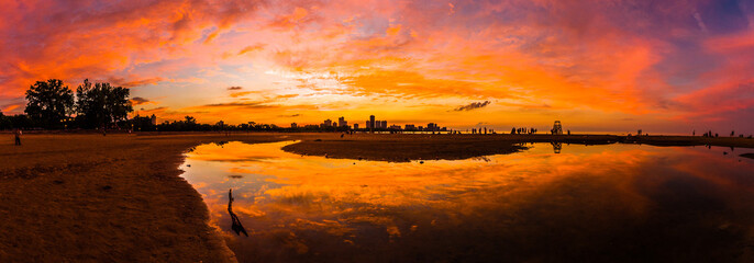 Beautiful, bright, saturated, and vivid sunset with colorful orange, yellow, blue, pink and purple clouds in the sky above reflecting on rain puddles in the sand at Montrose Beach in Chicago Illinois.