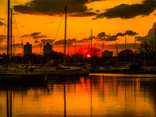 Gorgeous sunset with vivid colorful orange and yellow colored clouds in the sky above and boats reflecting in the water at Montrose Harbor in Chicago.