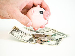 Photograph of a Caucasian male hand holding a pink ceramic piggy bank over a pile of united states paper money bills and coins isolated on a white background.