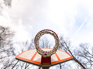 Close up unique photograph view looking up at an urban or city playground basketball net and hoop with the sky, clouds and tree branches above and orange and white backboard.