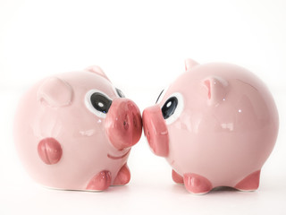 Close up photograph of two pink round pig ceramic salt and pepper shakers kissing or touching snouts facing each other isolated on a white background with space around the animal shaped objects.