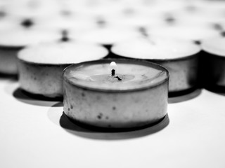 Closeup black and white photograph of lots of white tea candles in metal enclosure organized in rows with one used lit tea light making a beautiful spiritual, religious or romantic backdrop wallpaper.