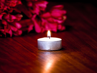 Romantic mood background photograph image of a tea candle with flame on a dark wood grain table and red flowers in the background.